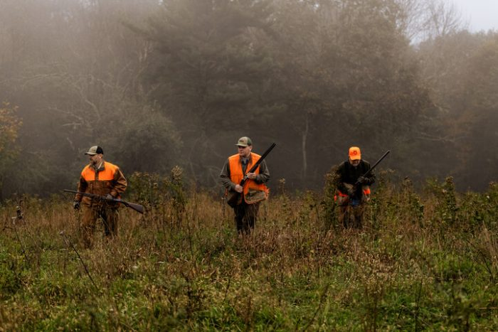 A photo of three men in blaze and camo hunting in West Virginia